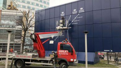 Montaż reklamy przy Warszawie Centralnej z użyciem podnośnika
