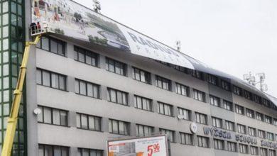 Montaż baneru reklamowego z podnośnika koszowego na budynku Wyższej uczelni
