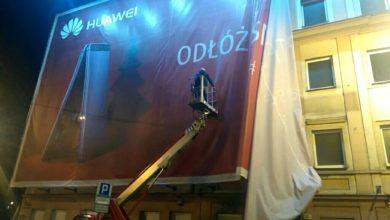 Podnośnik koszowy w akcji - montaż reklamy wielkoformatowej Huawei